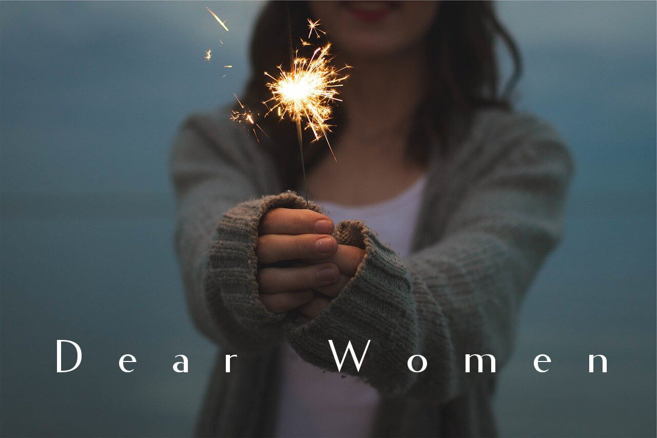 woman holding a sparkler toward the viewer with the nuff said essay title dear women